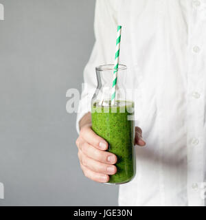 Young man holding bottle of green detox smoothie with drinking straw. Square crop. Concept of healthy lifestyle, - Stock Photo