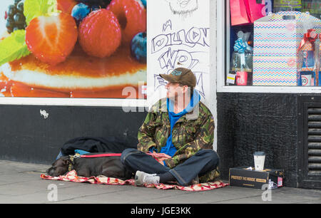 Homeless man with a dog sitting on a street in the UK. - Stock Photo