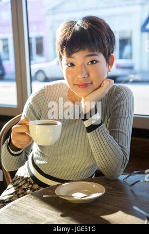 Serious Asian teenage girl drinking coffee in coffee shop
