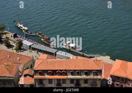 Roofs and traditional wooden boats  used to transport  Wine, on the Douro river in Gaia, Portugal. - Stock Photo