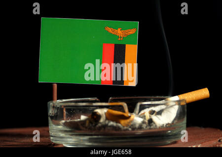 Zambia flag with burning cigarette in ashtray isolated on black background - Stock Photo