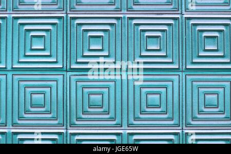 Old tiles on the wall with a unique square pattern, turquoise color. - Stock Photo