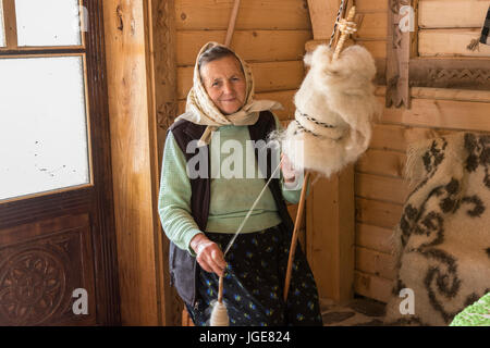 a woman spinning wool with a traditional method of the Maramures region, Romania - Stock Photo
