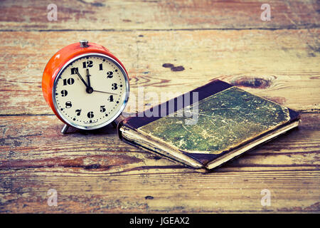 Time to read, old alarm and book on old wood floor - Stock Photo