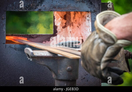 A blacksmith inserting steel rods into the hot oven  during medieval fair festival in Streatham Park in London - Stock Photo