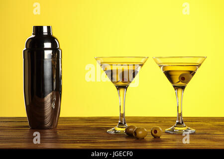 Two cocktails in martini glasses with green olives and shaker on a wooden surface against yellow background with - Stock Photo