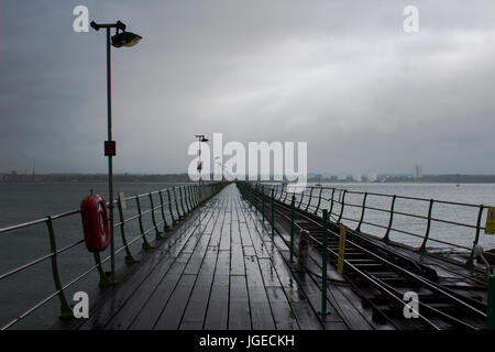 The long pier at Hythe in the south of England with its wooden walkway and railway line to the Southampton Ferry - Stock Photo