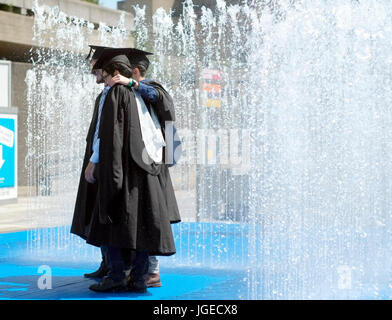 Graduates stand in a fountain, on a sunny day, after receiving their certificates in the Royal Festival Hall, on - Stock Photo