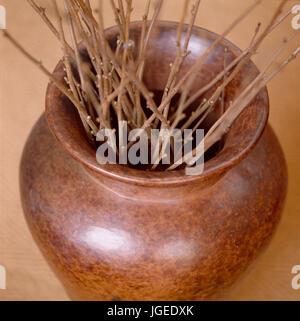 Closeup of polished wood vase holding twigs - Stock Photo