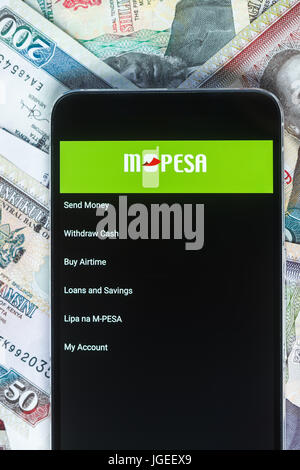 Safaricom M-Pesa fintech microfinance money transaction service on phone with Kenyan Shilling bank notes background - Stock Photo