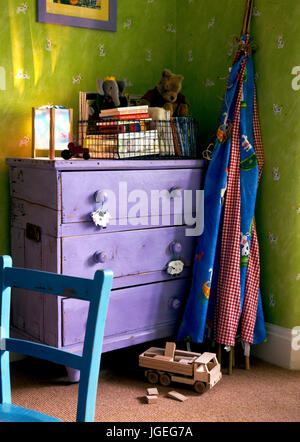 Corner of childrens room with purple painted chest of drawers and folded wigwam - Stock Photo