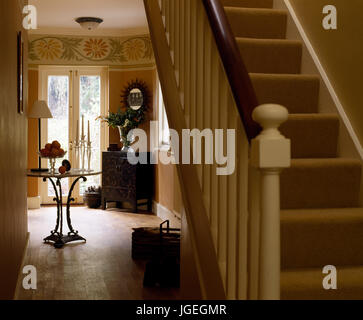 Staircase leading out of open plan hallway with hand-painted frieze - Stock Photo