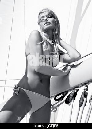 Beautiful blond female model sunbathing on a yacht in the sea - Stock Photo