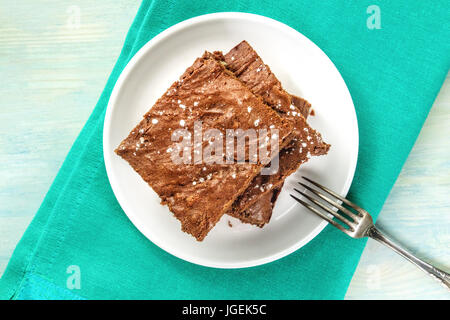 Overhead photo of chocolate brownies on teal textures - Stock Photo