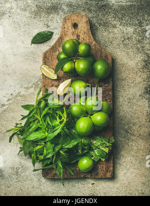 Flatlay of fresh limes and mint on rustic wooden board - Stock Photo