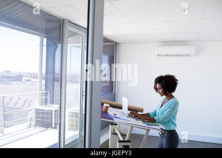 Female architect working over laptop in office - Stock Photo