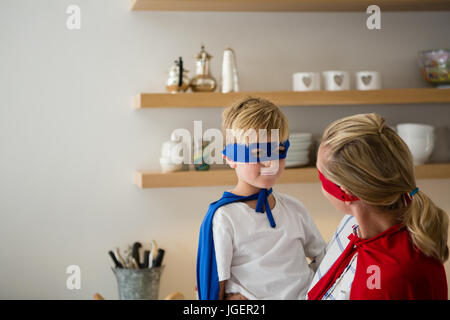 Mother and son pretending to be superhero in the kitchen at home - Stock Photo