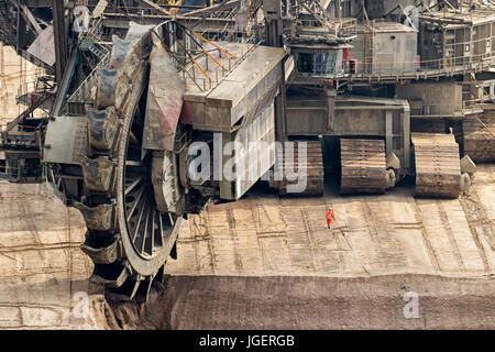 Bucket-wheel excavator mining in a brown coal open pit mine. - Stock Photo