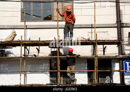 Chinese workers on scaffolding, Shanghai, China. - Stock Photo