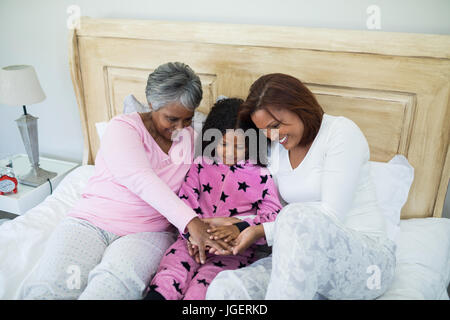 Happy family forming hand stack while playing on bed in bedroom - Stock Photo