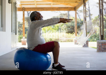 Active senior man exercising on exercise ball in the porch - Stock Photo