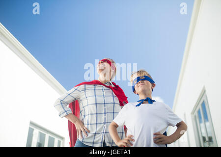 Smiling mother and son pretending to be superhero in garden - Stock Photo