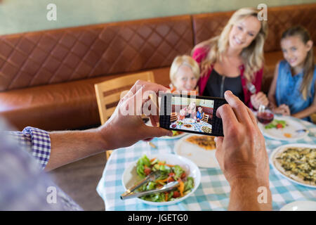 Cropped hand of father photographing family through smart phone at restaurant - Stock Photo