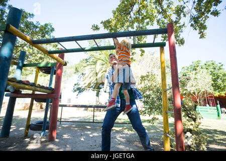 Low angle view of father assisting son in hanging on jungle gym at playground - Stock Photo