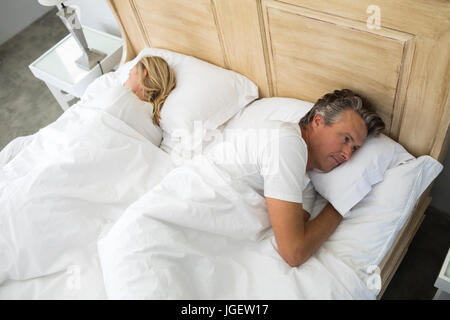 Couple lying on bed after having an argument in bedroom - Stock Photo