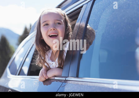 Cute girl looking out of the car window on a sunny day - Stock Photo