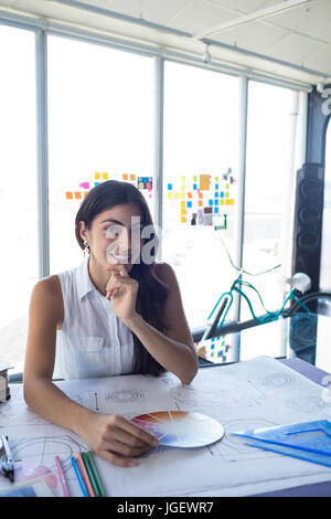 Female architect working on blueprint at her desk in office - Stock Photo