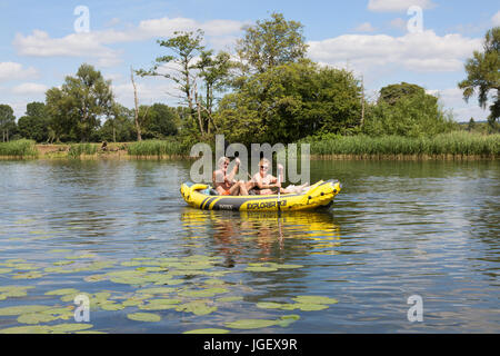 A midle aged couple rowing an inflatable canoe on the River Thames at Wallingford, Oxfordshire England UK - Stock Photo