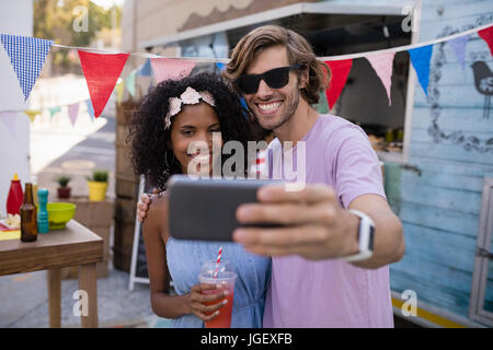 Happy couple taking selfie from mobile phone near food truck - Stock Photo