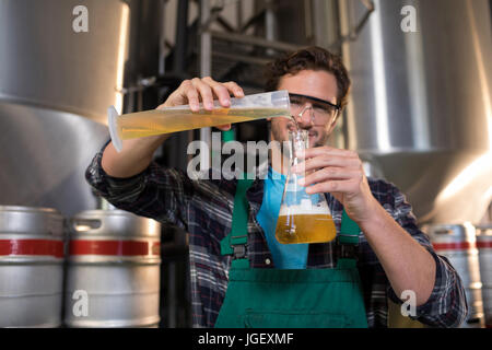 Portrait of smiling worker pouring beer in beaker at factory - Stock Photo