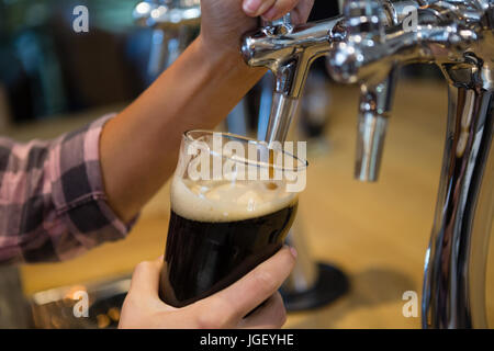 Cropped hands of barmaid pouring drink from tap in glass at bar counter - Stock Photo