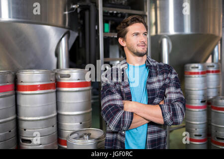 Thoughtful worker with arms crossed looking away while standing in factory - Stock Photo