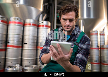 Worker using tablet computer while sitting in warehouse - Stock Photo