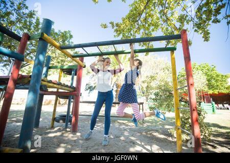 Happy mother talking to daughter hanging on jungle gym at playground - Stock Photo