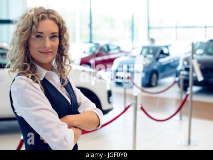 Portrait of smiling saleswoman standing in showroom - Stock Photo