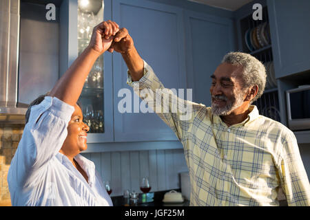 Affectionate couple dancing in kitchen at home - Stock Photo