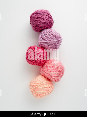 Knitting yarn balls in pink tone. Colored yarn on a white background. Skeins of wool yarn for knitting. - Stock Photo