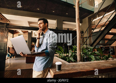 Shot of young business man thinking with laptop during break. Businessman in modern office using laptop. - Stock Photo