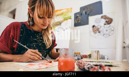 Shot of beautiful young female artist painting in studio. Woman painter drawing on paper in her workshop. - Stock Photo