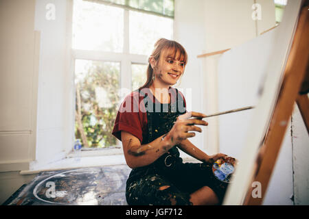 Indoor shot of female artist painting in studio. Woman painter painting in her workshop. - Stock Photo