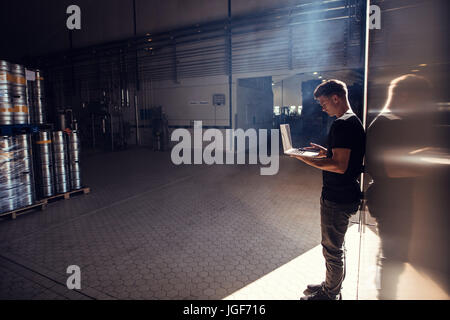 Horizontal shot of young man standing in brewery factory working on laptop. Brewery factory owner using laptop. - Stock Photo
