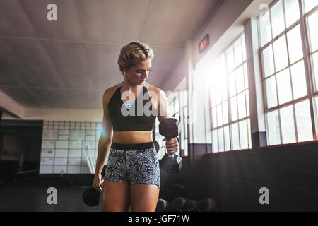 Young woman pumping muscles using dumbbells. Athlete excercising with dumbbells for muscle and strength building. - Stock Photo