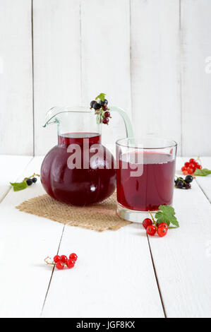 Cooling summer drink with berries - compote in a jug, glass on a white wooden background. Vertical view. - Stock Photo