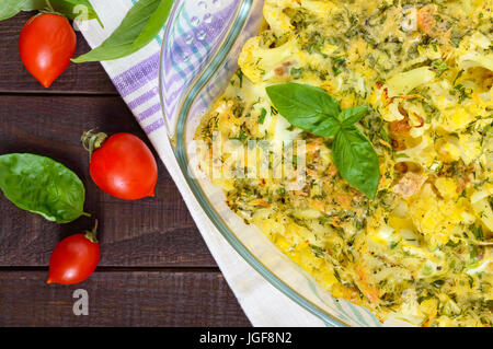Baked cauliflower with cheese and egg in a glass form on a dark wooden table. Top view. Close-up. Proper nutrition. - Stock Photo