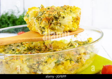 Baked cauliflower with cheese and egg in a glass form on a white wooden background. A large piece of casserole on - Stock Photo