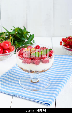 Sweet creamy dessert with granola, cream cheese, fresh raspberries in a glass bowl on a white wooden background. - Stock Photo